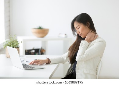 Young asian businesswoman touching massaging stiff neck to relieve pain in muscles after sedentary computer work in incorrect posture, japanese or chinese woman suffering from fibromyalgia at work