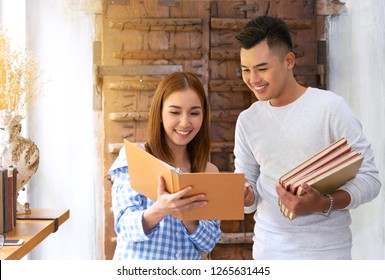 Young Asian businesswoman using books and document file to discuss information with businessman colleague in workplace. Two people discussion. Happy girl and boy reading books in library at university