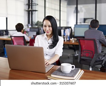young asian businesswoman working in office using laptop computer with colleagues in background.