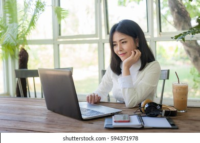 Young Asian businesswoman working online with laptop computer while sitting in coffee shop. Self-employed and freelance worker business activity concept
