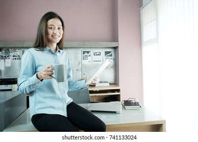 Young asian businesswoman working with tablet and holding a coffee cup with smiling face while sitting on office desk, casual office life concept