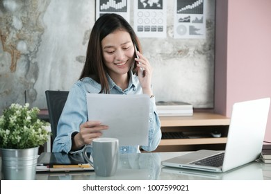 Young asian businesswoman working and talking phone at office table, business casual lifestyle