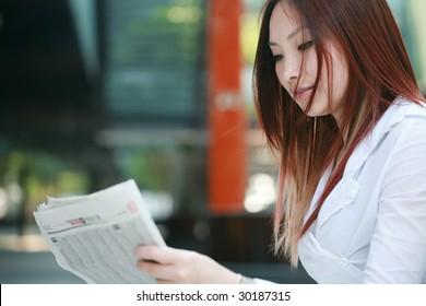 young asian businesswomen reading newspaer