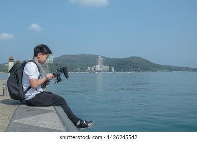 young asian camera man checking his files in camera