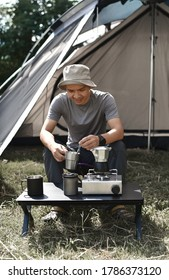 Le jeune campeur asiatique fait du café dans le camping en plein air.