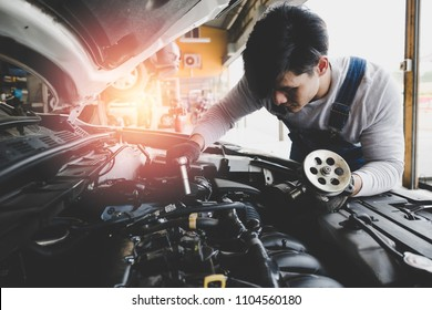 Young Asian car mechanic with spare parts working at service center repair