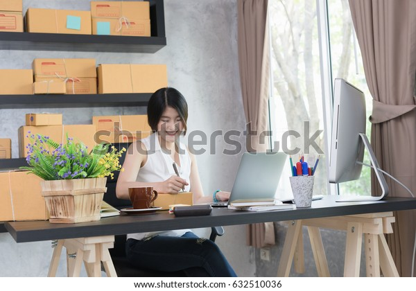 Young asian casual beautiful women entrepreneur, teenager business owner work at home, many stuff to do today in home. Note new order at box. Start up SME concept.