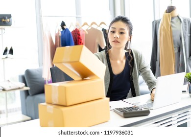 Young Asian casual business woman working small business online check her order in laptop computer for delivery to customer , SME and Delivery Concept ,Freelance Startup Home office, Shipping concept.