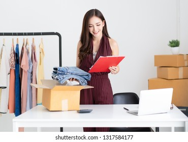 Young Asian casual woman working small business online packing jeans to cardboard box in home office. Startup Small business owner,Online selling, e-commerce, delivery, freelance working concept