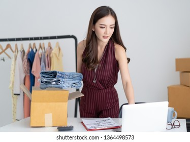 Young Asian casual woman working small business check her order in laptop computer and packing jeans to cardboard box in home office. Freelance Startup Small business owner,Online Selling, e-commerce.