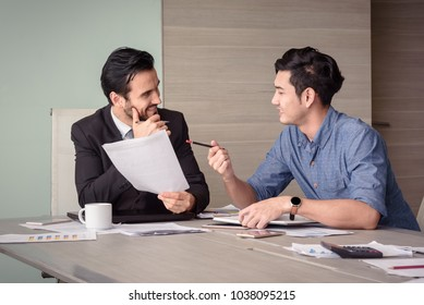 young asian and caucasian businessman discuss business project in meeting room office
