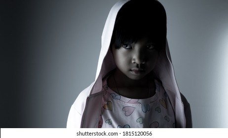 young Asian child girl in a robe has some scared and anxious faces in the dark.
