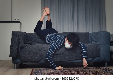 Young Asian child lying exhausted on sofa wearing a mouth mask (concept home quarantine)