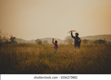 Young Asian children playing kites.happy family dad and child run on meadow with a kite in the summer on the nature