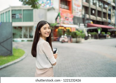 Young Asian Chinese business woman smiling and use digital tablet computer outdoor near office building,She has long black hair ,happiness girl with Summer sunny lifestyle fashion portrait on street