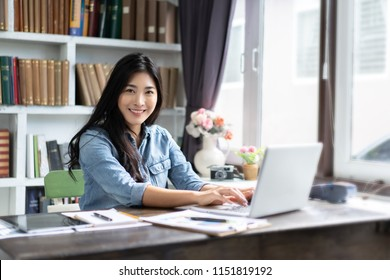 Young Asian Chinese businesswoman do document with a laptop in home office while smiling,technology for startup business concept,entrepreneur working modern living room ,work at home,freelance career