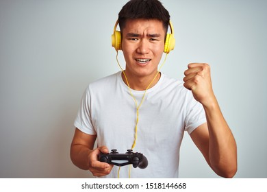Young asian chinese gamer man playing video game standing over isolated white background annoyed and frustrated shouting with anger, crazy and yelling with raised hand, anger concept
