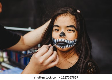 Young Asian Chinese girl with skeleton face make up. Make-up artist holding brush to paint mouth area. Skeleton design for chinese girl in Asia. Outdoor studio in the street. Drama competition.