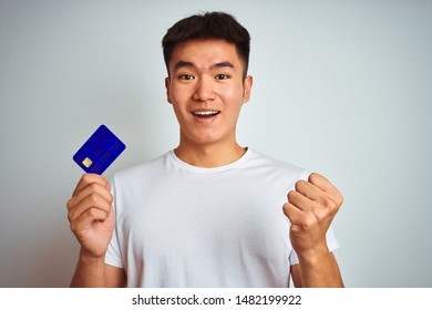 Young asian chinese man holding credit card standing over isolated white background screaming proud and celebrating victory and success very excited, cheering emotion