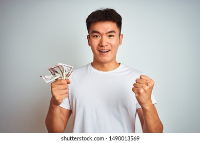 Young asian chinese man holding dollars standing over isolated white background screaming proud and celebrating victory and success very excited, cheering emotion