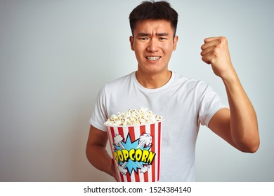 Young asian chinese man holding pack of popcorn standing over isolated white background annoyed and frustrated shouting with anger, crazy and yelling with raised hand, anger concept