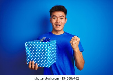 Young asian chinese man holding birthday gift standing over isolated blue background screaming proud and celebrating victory and success very excited, cheering emotion