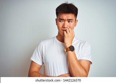 Young asian chinese man wearing t-shirt standing over isolated white background looking stressed and nervous with hands on mouth biting nails. Anxiety problem.