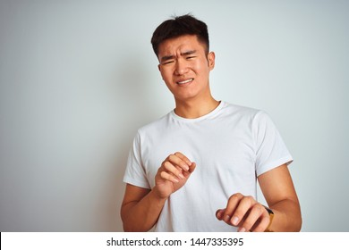 Young asian chinese man wearing t-shirt standing over isolated white background disgusted expression, displeased and fearful doing disgust face because aversion reaction. With hands raised.