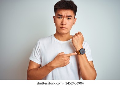 Young asian chinese man wearing t-shirt standing over isolated white background In hurry pointing to watch time, impatience, looking at the camera with relaxed expression