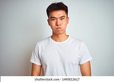 Young asian chinese man wearing t-shirt standing over isolated white background puffing cheeks with funny face. Mouth inflated with air, crazy expression.
