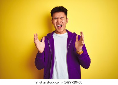 Young asian chinese man wearing purple sweatshirt standing over isolated yellow background celebrating mad and crazy for success with arms raised and closed eyes screaming excited. Winner concept