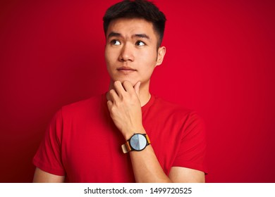 Young asian chinese man wearing  t-shirt standing over isolated red background serious face thinking about question, very confused idea
