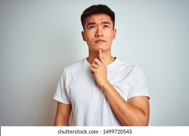 Young asian chinese man wearing t-shirt standing over isolated white background Thinking concentrated about doubt with finger on chin and looking up wondering