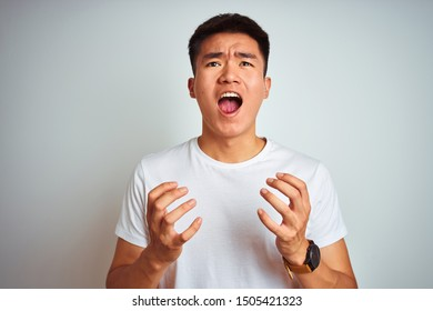 Young asian chinese man wearing t-shirt standing over isolated white background crazy and mad shouting and yelling with aggressive expression and arms raised. Frustration concept.