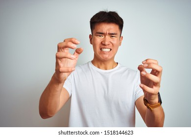 Young asian chinese man wearing t-shirt standing over isolated white background Shouting frustrated with rage, hands trying to strangle, yelling mad