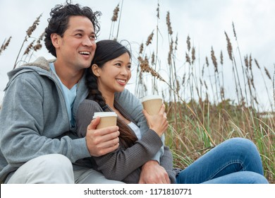 Young Asian Chinese man and woman, boy girl, couple with perfect teeth sitting on a beach drinking takeout cups of tea or coffee
