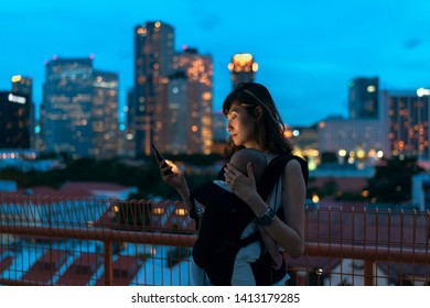 Young asian chinese mother traveling the city alone with baby in tow while working on the go