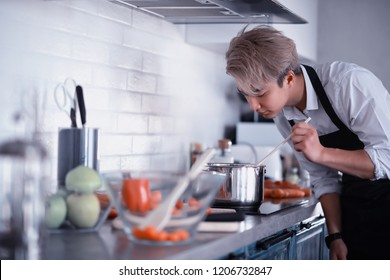 A young Asian cook in the kitchen prepares food in a cook suit