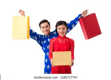 Young Asian couple in ao dai dresses with presents for Chinese New Year