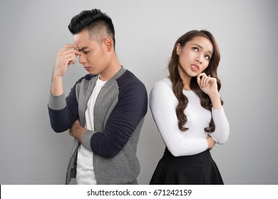 Young asian couple back to back ignoring bored and sad