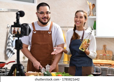 Young Asian couple blogger vlogger and online influencer recording video content on healthy food in the kitchen