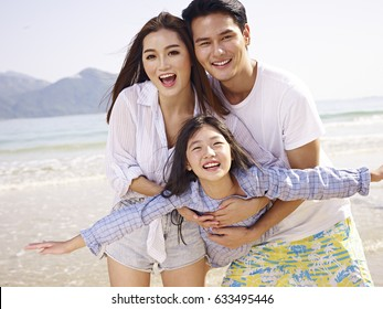 young asian couple carrying daughter having fun on beach.