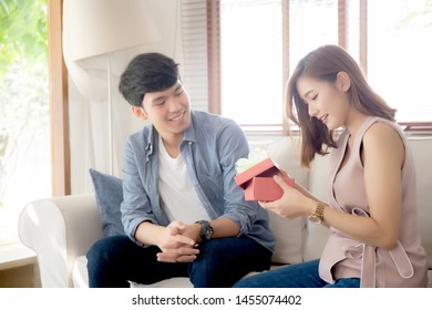 Young asian couple celebrate birthday together, asia man giving gift box present to woman for surprise at living room, female feeling happy and excited anniversary, holiday valentine concept.