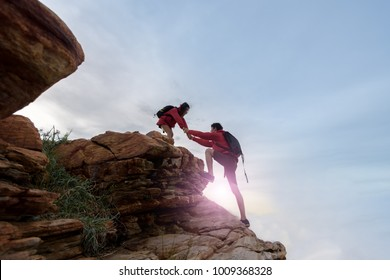 Young asian couple climbing up on the mountain,hiking teamwork ,success ,helps , business ,Together we can concept.