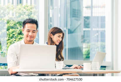 Young Asian couple or college student using laptop computer notebook work together at coffee shop or university campus. Information technology, cafe lifestyle, office meeting, or e-learning concept