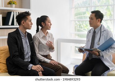A young Asian couple is consulting with a doctor about pregnancy planning.The doctor is reporting the health check-up to the couple and explaining the treatment guidelines, taking care of the health