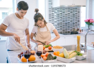 young asian couple cooking together in the kitchen at home.