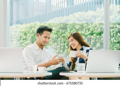 Young Asian couple, coworkers, or business partners have fun using smartphone together, with laptop computer at coffee shop. Information technology, cafe lifestyle, or romantic relationship concept