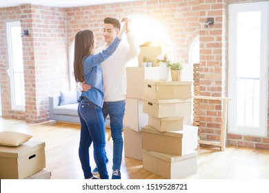 Young asian couple dancing and smiling celebrating moving to a new home