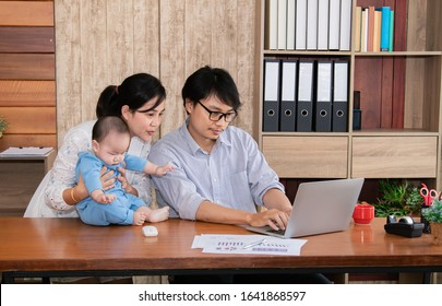 Young Asian couple entrepreneur with baby watching laptop for successful start up business at home office using technology internet information,  husband, wife together  run business or housing loan